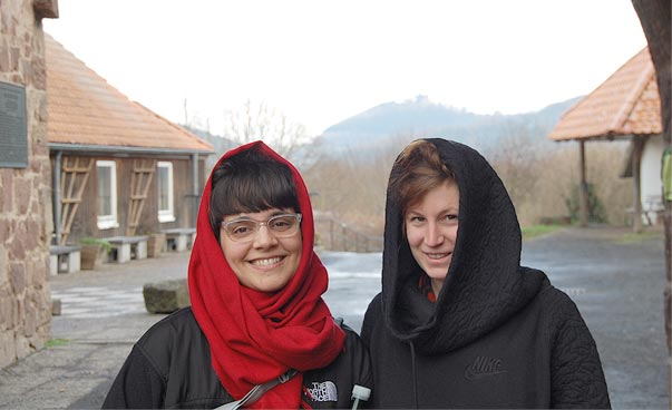 Two persons with hoods smile into the camera.