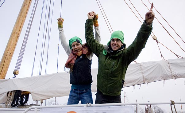 Two people raise their hands together. They are on a ship.