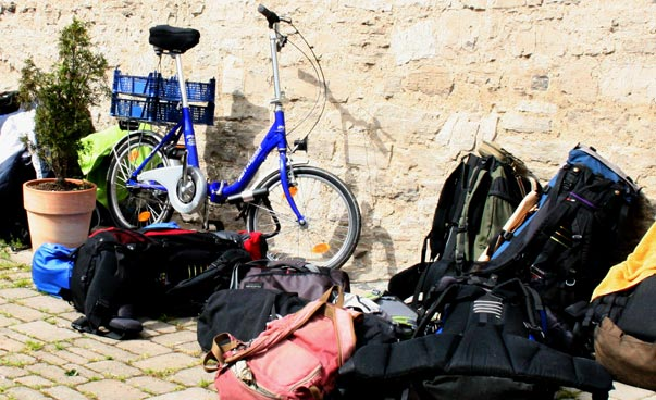 Luggage and a bicycle lean against a wall. Photo: Friedemann Wagner