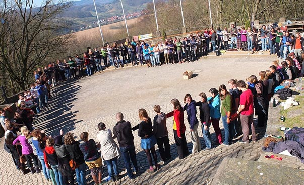 Many people stand outside in a large circle. Photo: Jens Marquardt